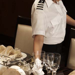 Yacht's Chief Stewardess or Butler setting a table