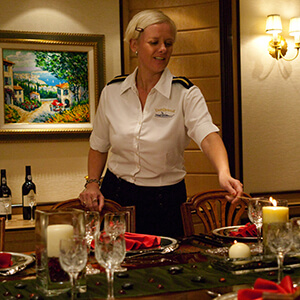 Yacht Stewardess lighting a candle at a dinner table